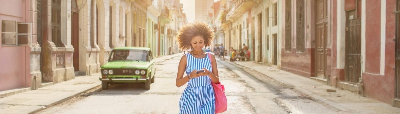 CAP Cuban girl looking at mobile phone, walking down street in Havana